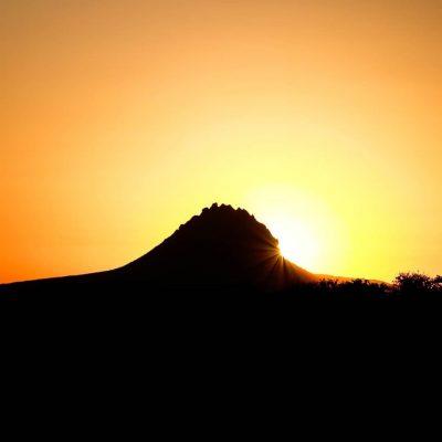 Cerro a lo lejos en ocaso tapando parte del sol